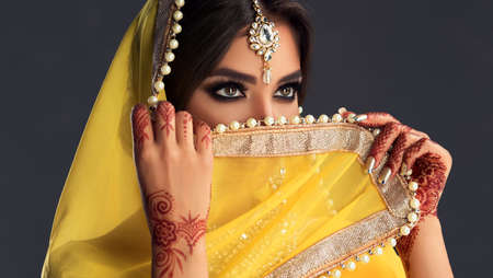 Black haired indian young woman dressed  in a posh yellow sari costume is hiding eyes behind traditional indian veil-dupatta. Indian tradition woman dress, henna-tattoo and stylish makeup. Reklamní fotografie - 152316325