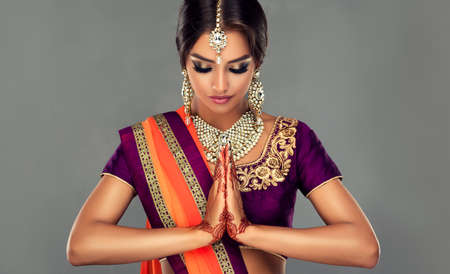 Perfect Indian woman is demonstrating welcome gesture. Portrait of beautiful indian girl dressed in a traditional national suit (sari), mehndi henna tattoo is painted on her hands.