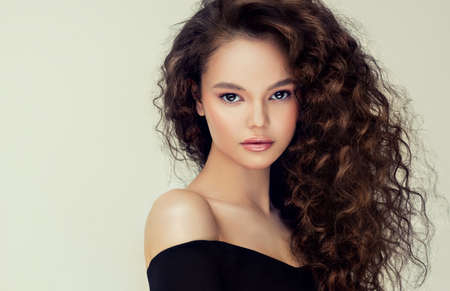 Young, brown haired woman with elegant, voluminous and frizzy hairstyle. Beautiful model with long, dense, curly hair and delicate makeup with rose lipstick. Hairdressing art. Reklamní fotografie - 153285674