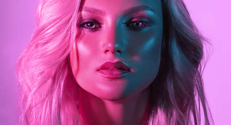 Portrait of young attractive model with face shaded in a different colors. Palette tints of  light on the face of attractive blond haired model. Makeup art and stylish blond hair.