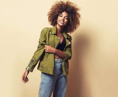 Wide toothy smile and expression of happiness on the face of young brown skinned woman dressed in the green stylish jacket, black top and blue jeans. Fashion and hairstyling.