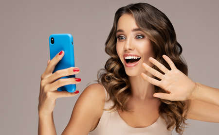 Hello friend! Young, toothy smiling woman is looking on the screen of smartphone. Look full of fun and joy on the face curly haired, tanned woman. Toothy smile and expression of happiness. Standard-Bild