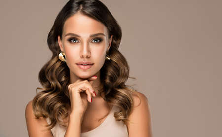 Portrait of beautifully looking young brown haired woman, dressed in a delicate evening makeup.Perfect model straightly gazing by kind, tender look at viewer. Beauty, elegance, hairstyling.
