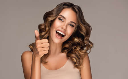 Thumb is up, everything is cool. Portrait of happily looking young model. Curly haired, tanned attractive woman is demonstrating positive emotions.