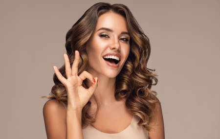 Laughing young woman is demonstrating sign is everything OKAY. Look full of fun and joy on the face curly haired, tanned woman. Toothy smile and expression of happiness.