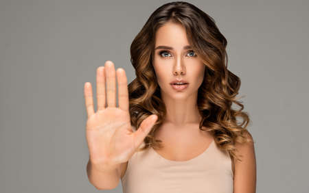 Young woman is holding palm in front of the camera.Stop it completely! Expression of alert and worryness on the  face of young woman. Demonstration of active social position. No agression.