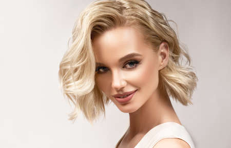 Portrait of beautiful looking young blonde woman with middle length hair, dressed in a delicate makeup.Perfect model looking aside. Beauty, elegance, hairstyling and cosmetics. Imagens