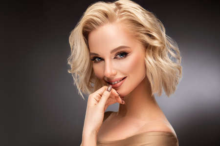 Beautiful looking young blonde woman with the middle length hair, wearing in a delicate makeup. Elegance and hairstyling.