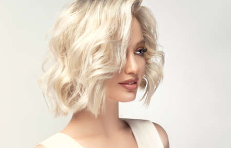 Elegant blonde hairstyle.Young blonde model with middle length hair dressed in a delicate makeup. Beauty, elegance, hairstyling and cosmetics. Imagens