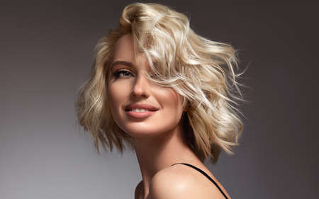 Portrait of beautiful looking young blonde woman with the middle length hair, wearing in a delicate makeup.Perfect model straightly gazing at the viewer with toothy smile.