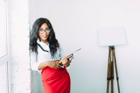 African-American business woman or teacher in glasses holding books and documents, standing on white background near big window 写真素材