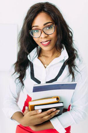 African-American business woman or teacher in glasses holding books and documents, standing on white background