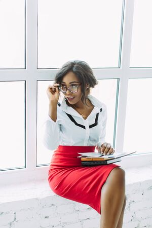 African-American business woman. Beautiful young african woman teacher sitting near the window