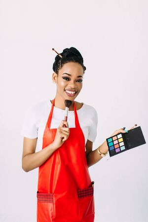Beautiful young African American beautician woman holding set of make up brushes and eye-shadows, isolated on white Stockfoto