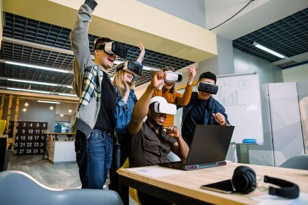Young cheerful team of young testers celebrating victory in a project while using VR glasses.