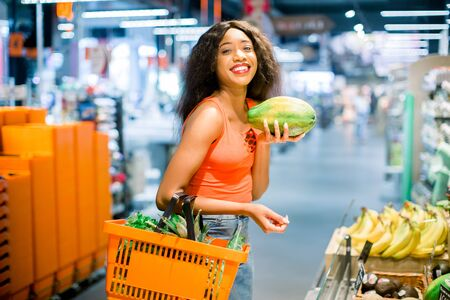 happy african american woman with shopping basket in vegetable and fruit department in supermarket