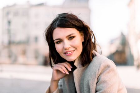 Lovely young woman, wearing in beige coat, with black short hair, posing on the street of old European city, on sunny day, close-up, copy space 写真素材