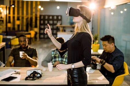 Woman in black clothes wearing VR goggles watched by her multiethnical colleagues in modern office