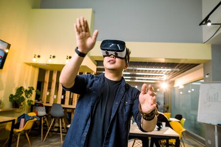 young asian man in casual clothes wearing head-mounted virtual reality goggles. Man with vr glasses posing in modern studio coworking. Reklamní fotografie