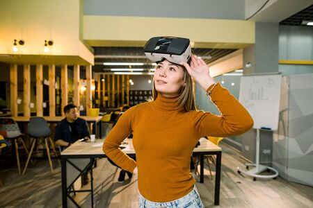 Woman in orange sweater and jeans wearing VR goggles watched by her multiethnical colleagues in modern office Stock fotó