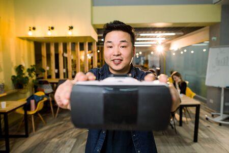 An Asian man holding virtual reality goggle on background of modern coworking studio office, his colleagues sitting at the table on the background. Reklamní fotografie