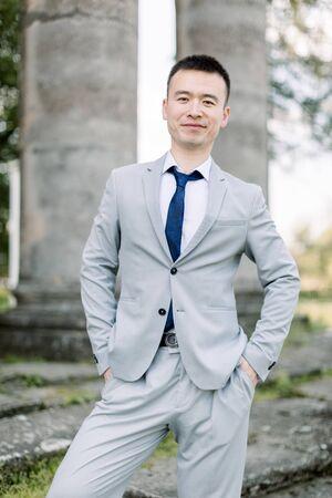 Eleganter lächelnder, gutaussehender asiatischer Bräutigam im grauen Anzug, der auf dem Hintergrund alter Steinsäulen im alten Schloss posiert