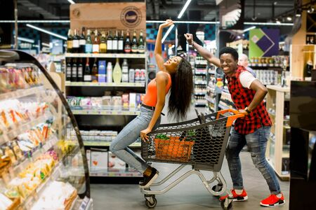 happy laughing african couple enjoys shopping dancing and driving with trolley in the supermarket