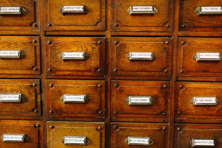 Old pharmacy drawer with latin names of drugs as a texture. Old vintage pharmacy cabinet closeup Stock Photo