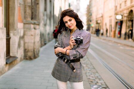 Mooie brunette jonge vrouw in mooie jas en witte broek, retro camera in handen houden. Mode foto op stedelijke achtergrond Stockfoto