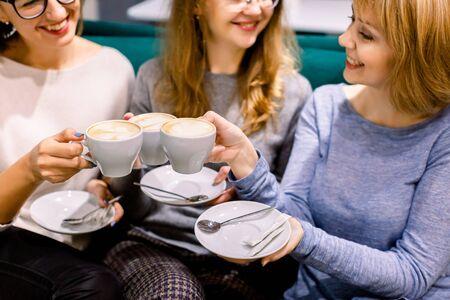 Gemeinsam Kaffee trinken. Blick von oben auf die schönen Frauen des Baumes, die Tassen Kaffee in den Händen halten und lächeln. Frauen im Café drinnen. Treffen der besten Freunde. Kaffee mit Kuchen Standard-Bild