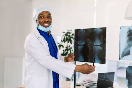 Medical office and doctor practice concept. Professional smiling african american doctor at clinic pointing on X-ray. Stok Fotoğraf