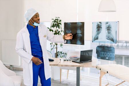 radiology, people and medicine concept - young African American man doctor looking at x-ray images of parients at hospital