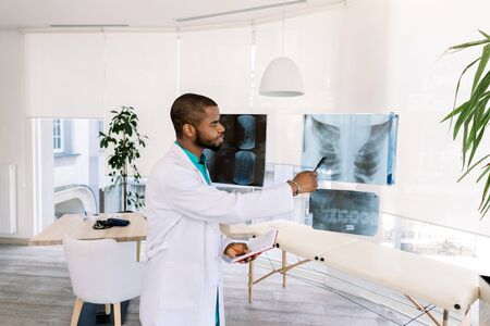 african american man doctor in medical uniform with x-ray. Young professional African-American doctor examining x-ray of patients chest