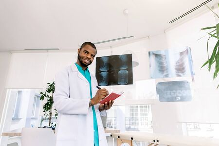 health and medicine concept - smiling African man doctor studying x-ray of the patients while standing in modern medical office
