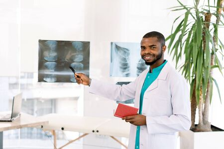 Young male african american health care worker doctor in white coat standing in modern clinic office and looking at patient x-ray