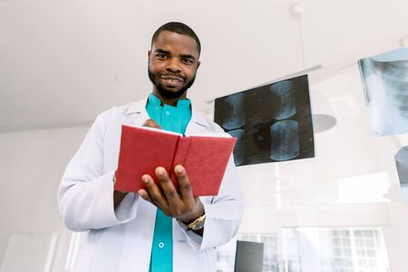 Portrait of a young African man doctor in medical costume, looking at camera, holding red otebook and pen, standing in modern office with a radiography on the background