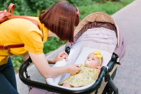 Pretty baby girl in yellow dress in stroller smiling to her mother