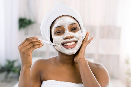 vitamin facial mask. African smiling woman with a face in a mask in spa.