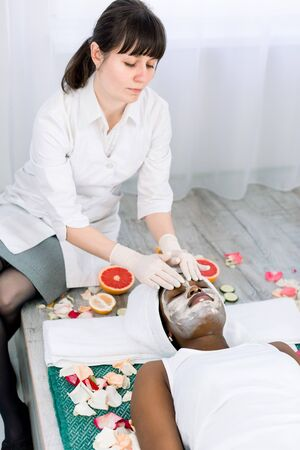 Face peeling mask, spa beauty treatment, skincare. Pretty African woman getting facial care by beautician at spa salon.