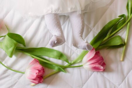 A little beautiful newborn girl in a white dress is lying on the bed among the flowers