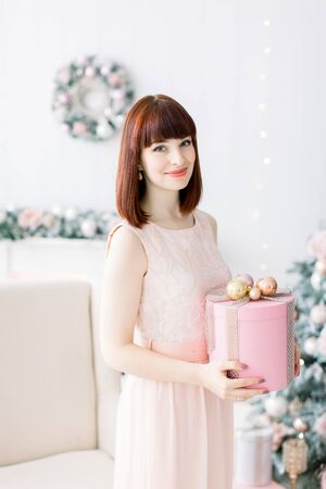 Smiling pretty young woman in light orange pink dress holding christmas present box and standing in beutiful cozy living room with Christmas decorations