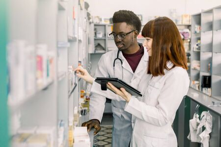 Confident Male And Female Pharmacists In Pharmacy. female pharmacist talking with her colleague about the attributes and side effects of a medicine or pharmaceutical product for sale, in the pharmacy.