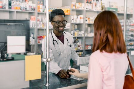 smiling male Afrcian pharmacist giving medicine to young Caucasian woman in drugstore. Standard-Bild
