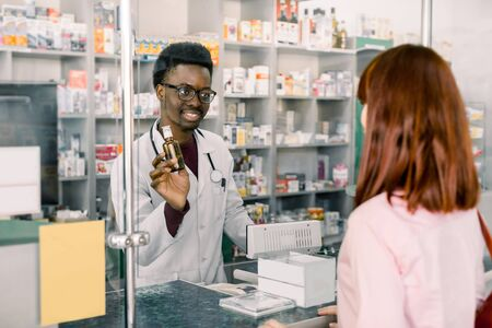 medicine, pharmaceutics, health care and people concept - happy young African man pharmacist giving drug to young pretty woman customer at drugstore.