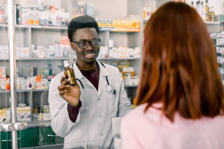 African man Pharmacist and woman client at pharmacy.