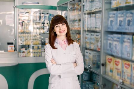 Cheerful young smiling Caucasian pharmacist chemist woman standing in pharmacy drugstore.