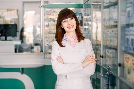 Portrait of a smiling young woman pharmacist with arms crossed at modern pharmacy. Beautiful woman wearing in white lab coat working in drugstore