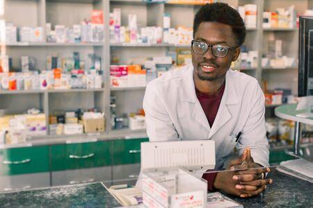 Experienced African American man pharmacist in white coat working in modern pharmacy.