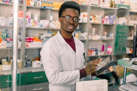 Confident African American man pharmacist standing in interior of pharmacy