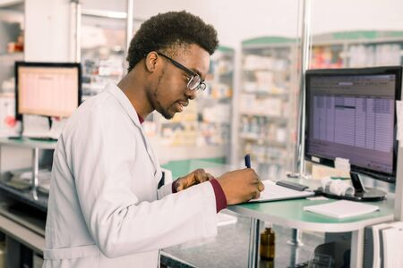 Experienced African American male pharmacist working on pc in modern pharmacy and writing working notes.